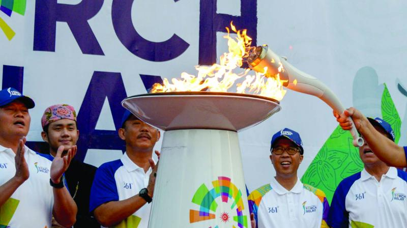 Officials light the 2018 Asian Games torch in Jakarta on Wednesday. Jakarta and Palembang will host some 11,000 athletes and 5,000 officials from 45 Asian countries for the Asian Games, which will commence on Saturday. Below:  Dancers perform at the relay ceremony. (Photo: AFP)