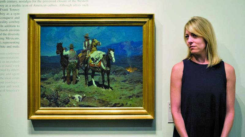 """Chief curator Amy Scott pauses for photos with a painting titled """"First Streak of Dawn"""" by Frank Tenney Johnson at the Autry Museum, in Los Angeles. (Photo: AP)"""