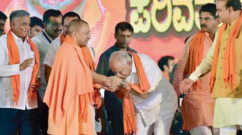 UP CM Yogi Adityanath (left) is greeted by BJP Karnataka unit chief B.S. Yeddyurappa during the party's Parivartan Rally in Bengaluru. (Photo: PTI)