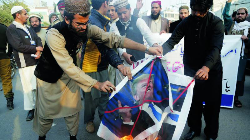 Pakistani protesters burn posters of US President Donald Trump in Lahore. (Photo: AP)
