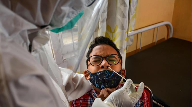 A young man gets a free swab test by a university laboratory amid the COVID-19 coronavirus outbreak at a community health centre. AFP