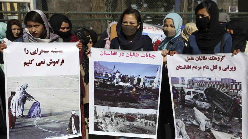 Afghan civil society activists hold banners with Dari. AP Photo