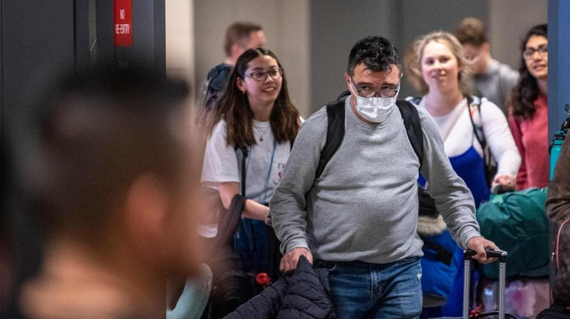 A passenger arriving from Brussels wearing a mask to protect himself from the new coronavirus looks for his relatives in the International arrivals zone at Dulles airport outside Washington. AFP Photo