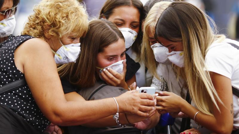 Travelers wearing protective masks look at a smart phone at the Ministro Pistarini International Airport, in Ezeiza. AP Photo