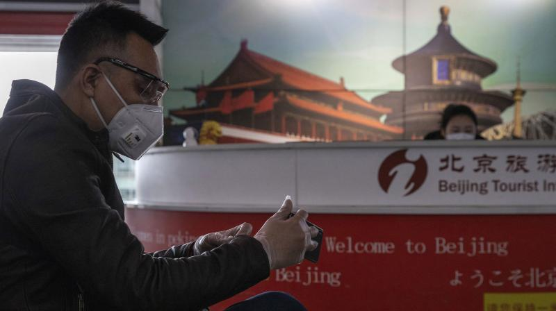 A traveler waits near a tourist information booth at the Capital International Airport terminal 3 in Beijing. AP Photo