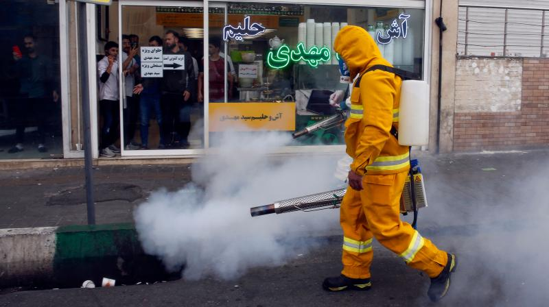 An Iranian firefighter disinfects a street in the capital Tehran in a bid to halt the wild spread of coronavirus. AFP Photo