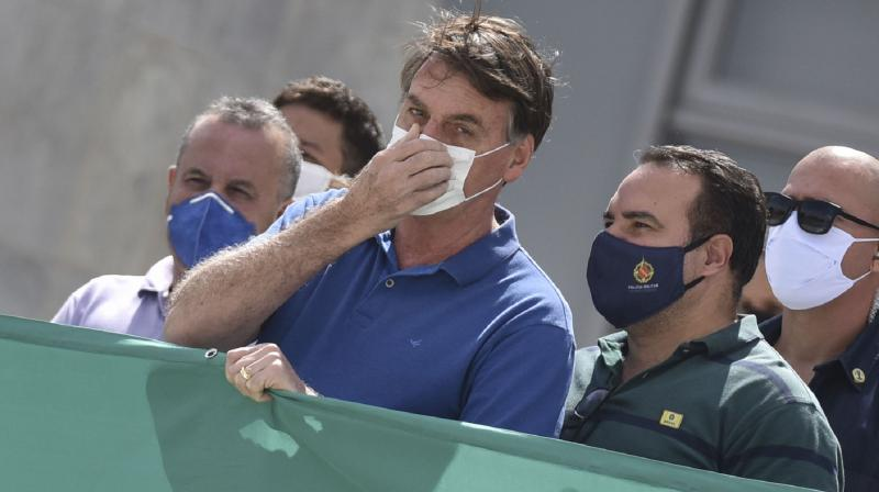 In this May 17, 2020 file photo of Brazil's president Jair Bolsonaro, wearing a protective face mask as a precaution against the spread of the new coronavirus. A profanity-laced video showing Bolsonaro expressing frustration at his inability to get information from police and vowing to change Cabinet ministers if needed to protect his family was released on Friday, May 22, 2020, at the order of a Supreme Court justice in a new blow to a president whose popularity has been sagging. (AP)