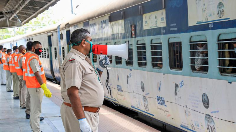 Police personnel stand guard as a train carrying migrants from Mumbai arrives at Jashidih station in Deoghar. (PTI)