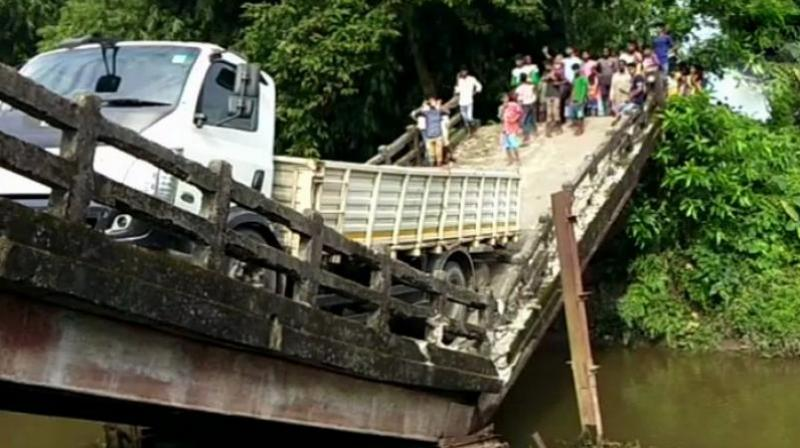 The truck is still hanging from the broken portion of the bridge that connects Manganj area to Siliguri, a major city in north Bengal. (Photo: Twitter | ANI)