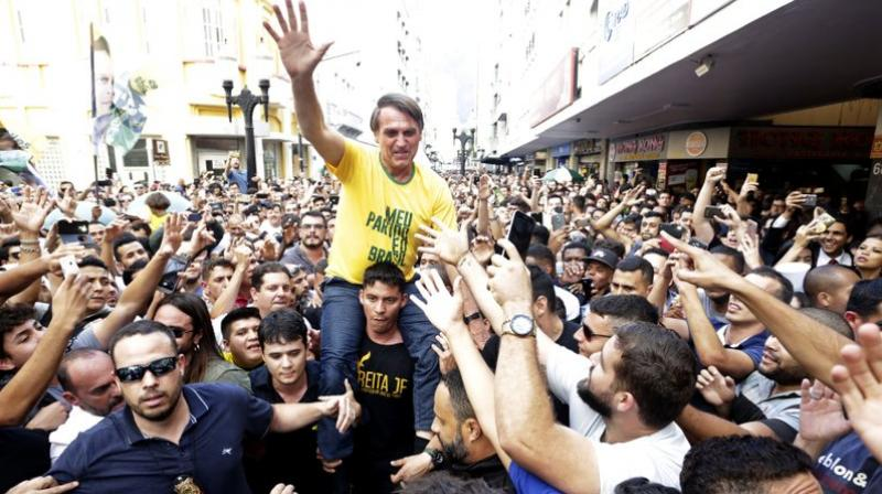 Presidential candidate Jair Bolsonaro is taken on the shoulders of a supporter moments before being stabbed during a campaign rally in Juiz de Fora, Brazil. (Photo: AP)
