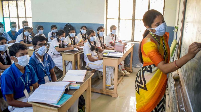 Students wearing anti-pollution masks attend a class in Gurgaon on Saturday. (Photo: PTI)