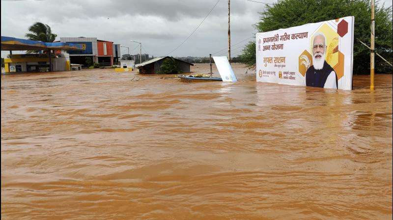A billboard with a photograph of Prime Minister Narendra Modi is partially submerged in flood waters at Kolhapur in western Maharashtra on Saturday, July 24, 2021. Officials say landslides and flooding triggered by heavy monsoon rain have killed more than 100 people in western India. (AP)