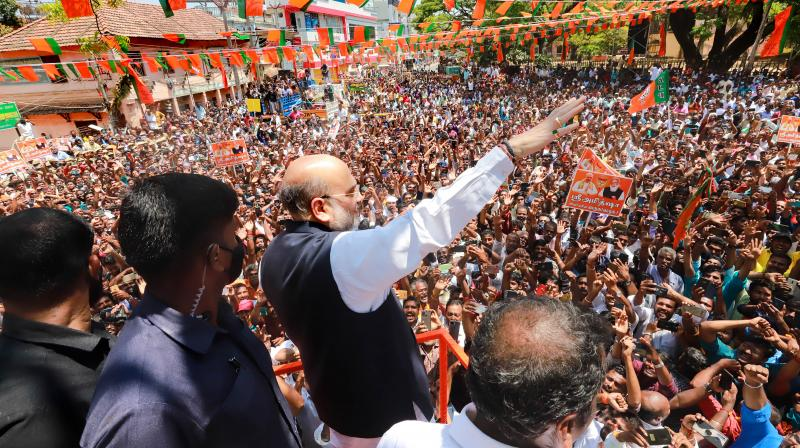 Union Home Minister and senior BJP leader Amit Shah waves at supporters during his election campaign roadshow at Nagercoil, Kanyakumari, Sunday, March 7, 2021. (PTI)