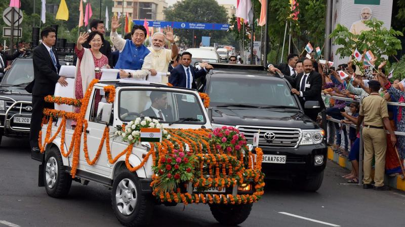 Prime Minister Narendra Modi, Japanese Prime Minister Shinzo Abe and his wife Akie Abe ride an open vehicle during their roadshow in Ahmedabad. (Photo: PTI)