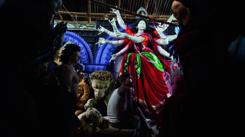 An artisan takes a break as he makes idols of goddess Durga ahead of Durga Puja festival in Gauhati. (Photo: AP)