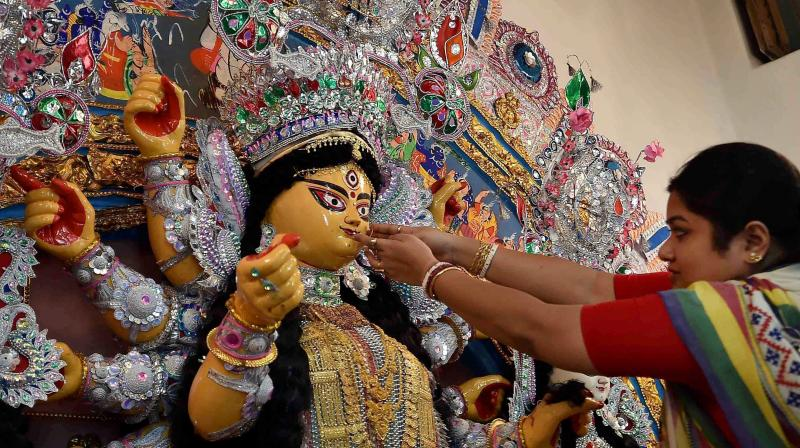 An idol of Goddess Durga being being decorated with gold ornaments during Durga Puja festival in Kolkata. (Photo: PTI)