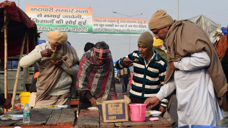 Farmers having breakfast during their ongoing protest against the new farm laws, at Ghazipur border in New Delhi, Friday, January 29, 2021. (PTI /Kamal Kishore)