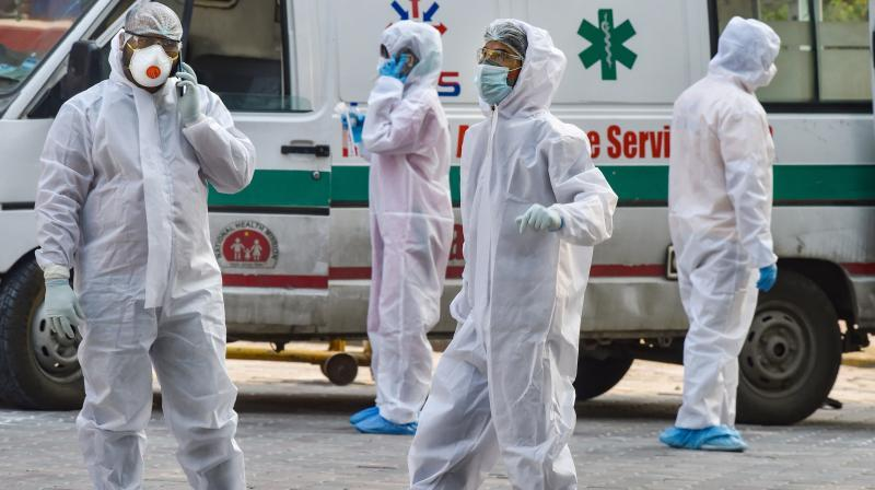 Health workers wearing protective suits are seen in the premises of LNJP Hospital during the nationwide lockdown, in wake of the coronavirus pandemic, in New Delhi.