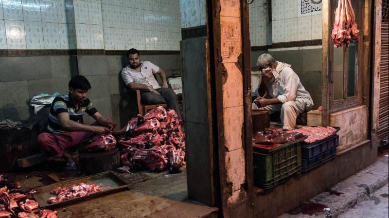 Indian butchers work in their shop as they prepare buffalo meat for sale in New Delhi. (AFP Photo)