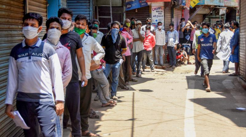 People queue up at a doctor's clinic to get a medical certificate in Dharavi, Mumbai. PTI photo