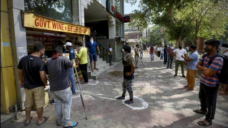 Indians line up to buy liquor outside one the liquor shops which was reopened Monday. (AP)