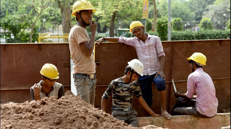 Indian labourers work at a construction site on a roadside in New Delhi. India's 2018-19 jobless rate declines to 5.8%. (AFP Photo)