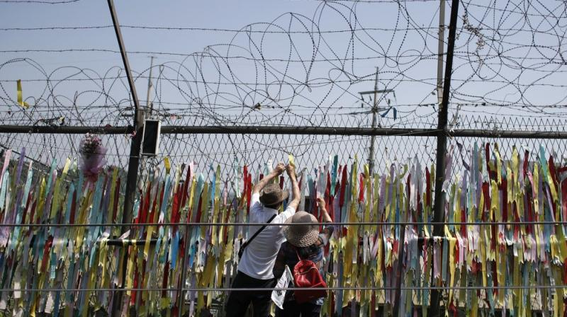 Visitors hang a ribbon on a wire fence decorated with other ribbons at the Imjingak Pavilion in Paju, South Korea, Tuesday, June 9, 2020. North Korea said Tuesday it will cut off all communication channels with South Korea as it escalates its pressure on the South for failing to stop activists from floating anti-Pyongyang leaflets across their tense border. (AP Photo)