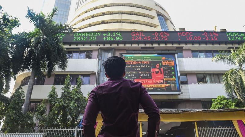 A bystander watches the stock prices displayed on a digital screen at the facade of the Bombay Stock Exchange (BSE) building, in Mumbai. (PTI Photo)
