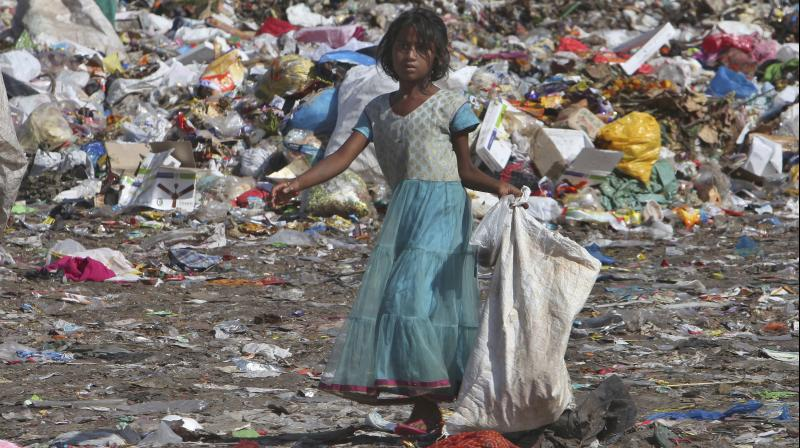 An Indian ragpicker collects reusable material from a garbage dump. Coronavirus pandemic could plunge an extra 395 million people into extreme poverty. (AP Photo)