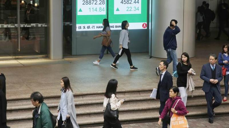 People walk past an electronic board showing Hong Kong share index outside a bank in Hong Kong. (AP Photo)