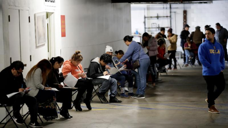 Unionized hospitality workers wait in line in a basement garage to apply for unemployment benefits. (AP Photo)