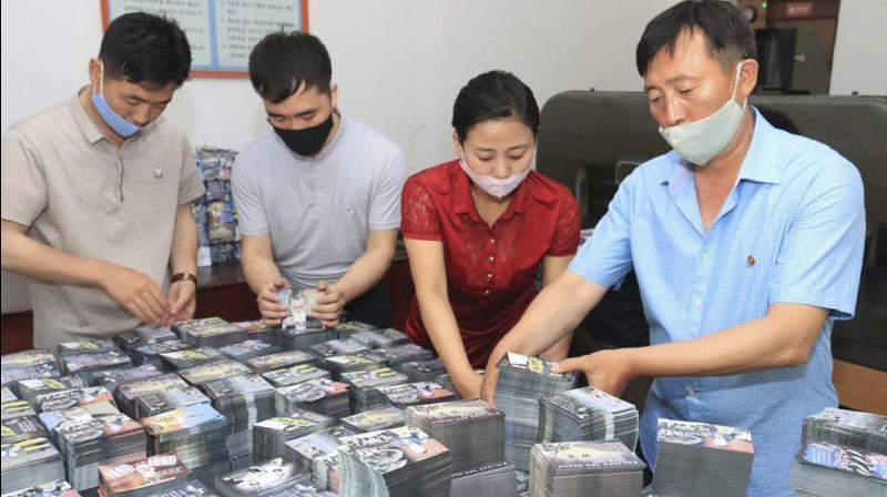 North Korean government shows North Koreans prepare anti-South Korea propaganda leaflets in North Korea. South Korea on Monday, June 22, 2020 urged North Korea to scrap a plan to launch propaganda leaflets across the border. (Korea News Service via AP, File)