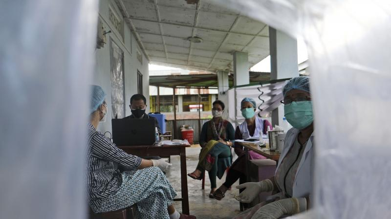 Health workers sit behind a plastic sheet separating them from people receiving the COVID-19 vaccine In Imphal, India, Monday, June 21, 2021. (AP)