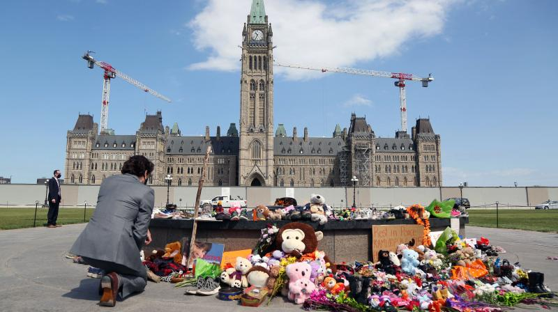 Canadian Prime Minister Justin Trudeau visits the makeshift memorial erected in honor of the 215 indigenous children remains found at a boarding school in British Columbia, on Parliament Hill June 1, 2021 in Ottawa. (AFP file photo)
