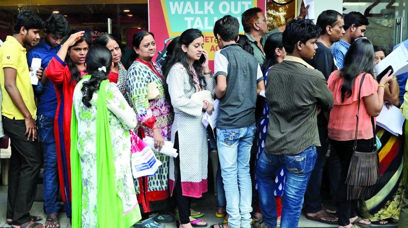 People queue up outside a private bank at Currey Road to access their money on Monday. (Shripad Naik)