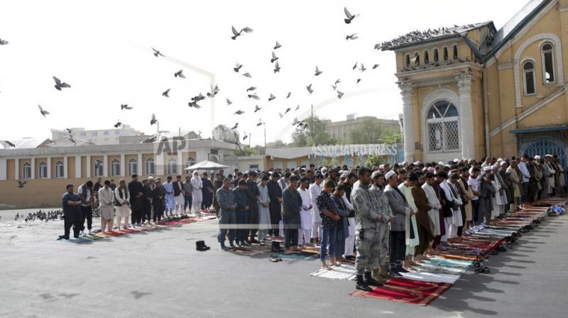 People attend Eid al-Fitr prayers outside of Shah-e-Dushamshera mosque in Kabul. Taliban, an insurgent group who fight against NATO and Afghanistan's government, announced that they will start a 3-day ceasefire, starting in the first day of Eid al-Fitr. (Photo: AP)