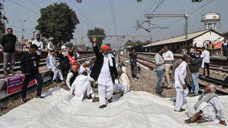 Protesting farmers sit on tracks after calling for a four-hour rail blockade as they continue their protest against the central government's recent agricultural reforms, in Sonipat on February 18, 2021. (AFP)