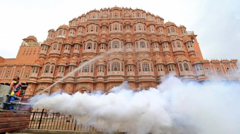 JMC workers fumigate the area around Hawa Mahal as a precautionary measure to contain the spread of coronavirus, during the nationwide lockdown, in Jaipur. PTI photo