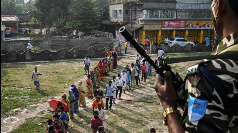 A paramilitary personnel stands guard as people wait to cast their votes at a polling station during the state legislative elections, at South Twenty Four Parganas district, about 70 km from Kolkata on April 6, 2021. (Dibyangshu Sarkar / AFP)
