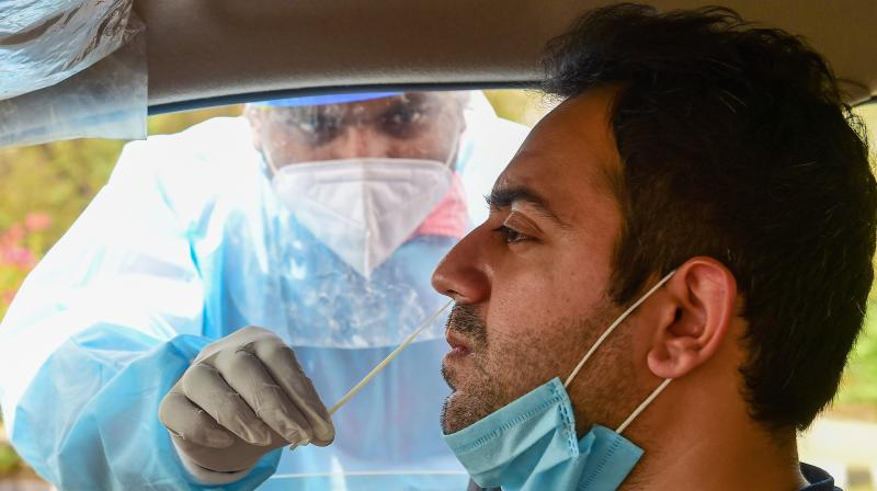 A health worker collects samples of a motorist for Covid-19 tests, as coronavirus cases spike across the country, in New Delhi on April 5, 2021. (PTI/Kamal Kishore)