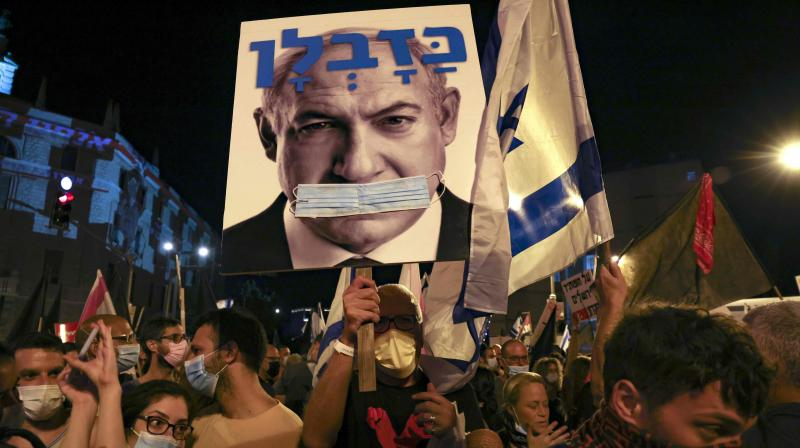 Israeli protesters hold a poster of their prime minister Benjamin Netanyahu gagged by a surgical protection mask during an anti-government demonstration in front of Netanyahu's residence in Jerusalem on September 12, 2020, demanding his resignation over several corruption indictments and his handling of the coronavirus crisis. (AFP)
