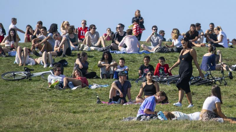 People enjoying the autumn sunshine on Primrose Hill, London, Sunday, Sept. 13, 2020. From Monday, social gatherings of more than six people will be banned in England both indoors and outdoors and Boris Johnson hinted that such restrictions will potentially remain in place until or through Christmas. (AP)