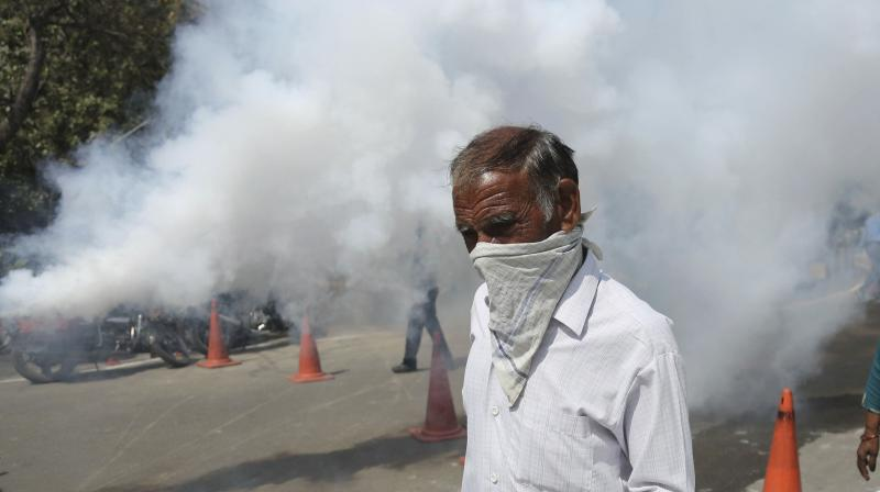 A man covers his face with a handkerchief as municipal workers spray disinfectant as a precautionary measure against COVID-19 outside at the Government Medical College in Jammu on March 19, 2020. (AP)