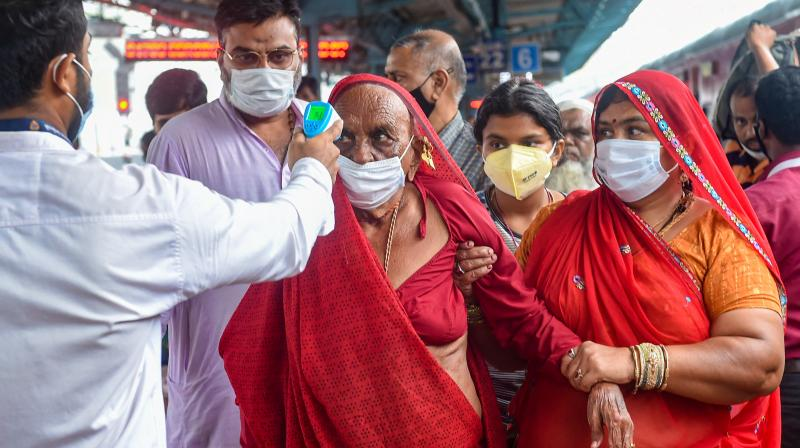 A BMC health worker does thermal screening of a passenger for COVID-19 test, at Dadar railway station in Mumbai, Wednesday, Aug. 18, 2021. (PTI/Shashank Parade)