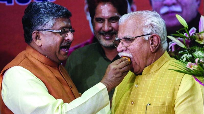 Incumbent Haryana chief minister Manohar Lal Khattar being offered sweets by Union minister Ravi Shankar Prasad after he was elected as the leader of BJP Legislature party in Chandigarh. (Photo: PTI)