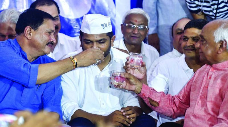 Patidar leaders offer coconut water to PAAS leader Hardik Patel to break his 19-day hungerstrike in Ahmedabad on Wednesday. (Photo: PTI)