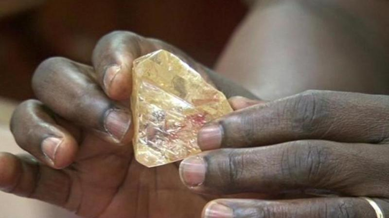 In this photo taken from video footage, Sierra Leone's President Ernest Bai Koroma hands a diamond during a meeting with delegates of Kono district, where the gem was found, at the presidential office in Freetown, Sierra Leone. (Photo: AP)