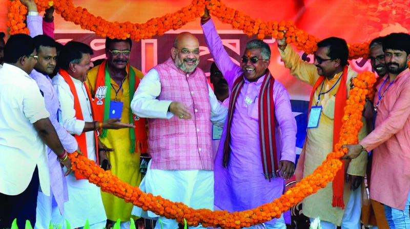BJP chief Amit Shah garlanded by his party workers during an election campaign in in West Midnapore on Tuesday.  (Photo: PTI)