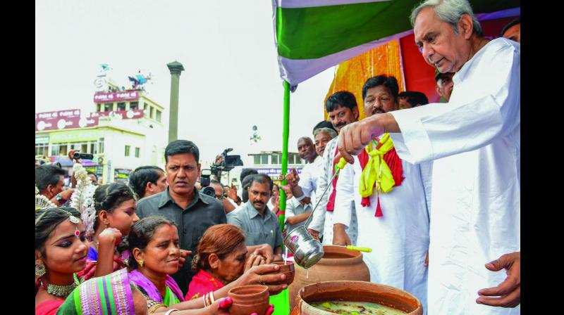 "Odisha chief minister Naveen Patnaik distributes ""Abhada Torani"" to devotees during the annual Rath Yatra in Puri on Thursday. (Photo: PTI)"