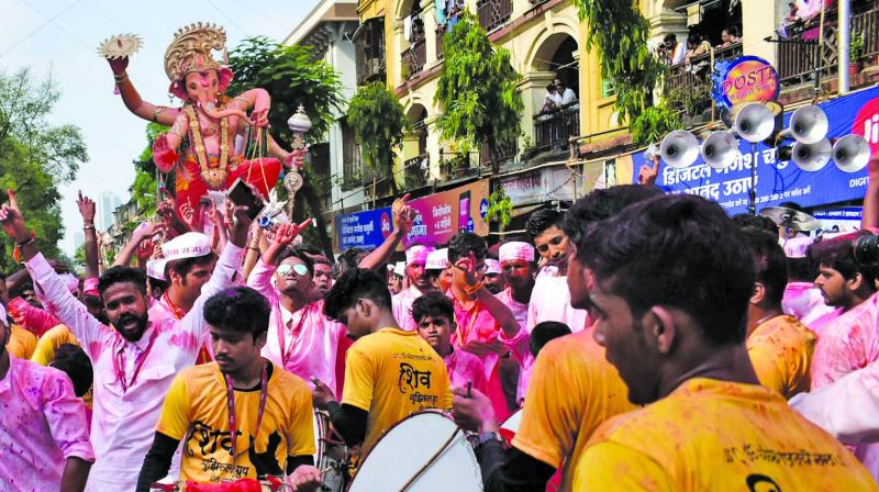 Devotees take a giant idol of 'Ganesh Galli' through the streets to immerse in the sea. (Photo: Debasish Dey)